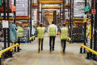 Staff in reflective vests walking from camera in a warehouse