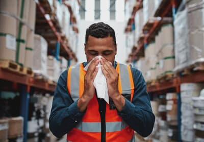 Young sick african warehouse worker blowing nose while working wearing safety vest